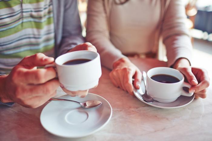 [Deux adultes tenant des tasses de café]