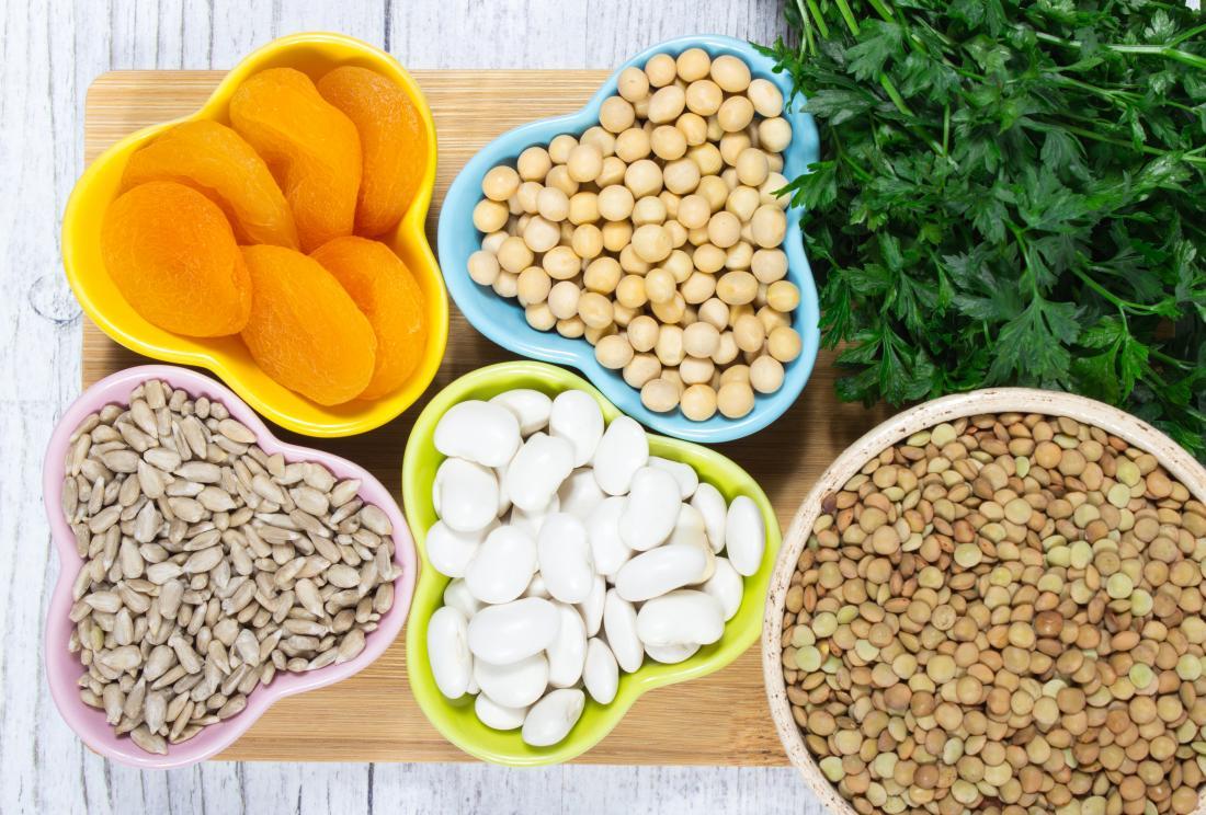 乾燥したアプリコット、豆、種子、ヒヨコマメ、レンズ豆、緑色の葉野菜を含む鉄分豊富な食品。