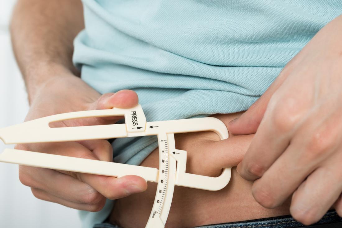 Homem medir a gordura da barriga.