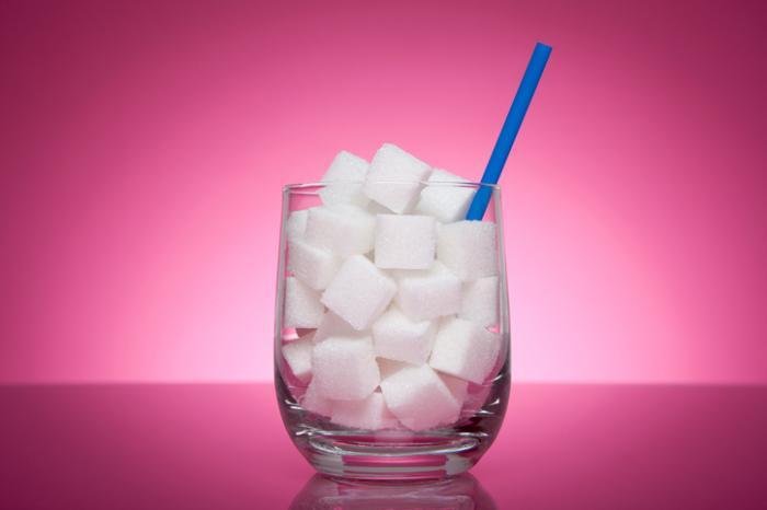 Un bicchiere pieno di cubetti di zucchero e una cannuccia.