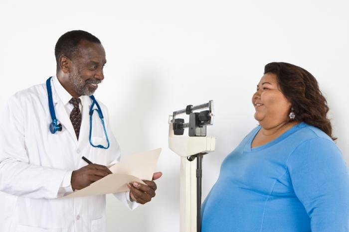Um médico fala com uma mulher obesa em algumas escalas.
