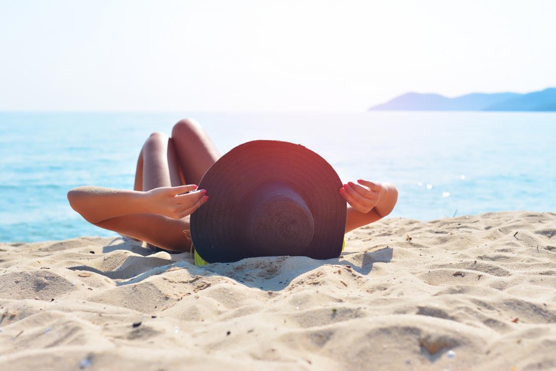 薄い皮を増やすかもしれないビーチで日光浴する女性