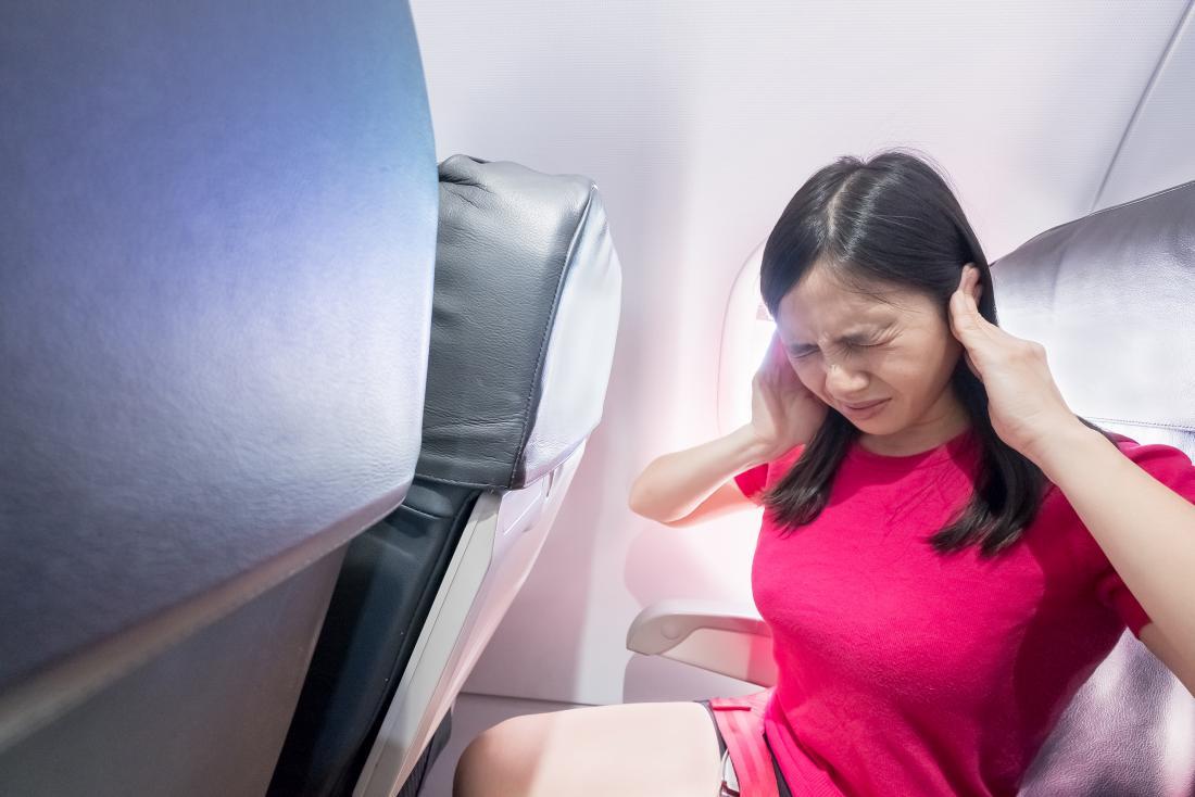 Fille avec des oreilles douloureuses dans un avion se demandant comment faire éclater vos oreilles