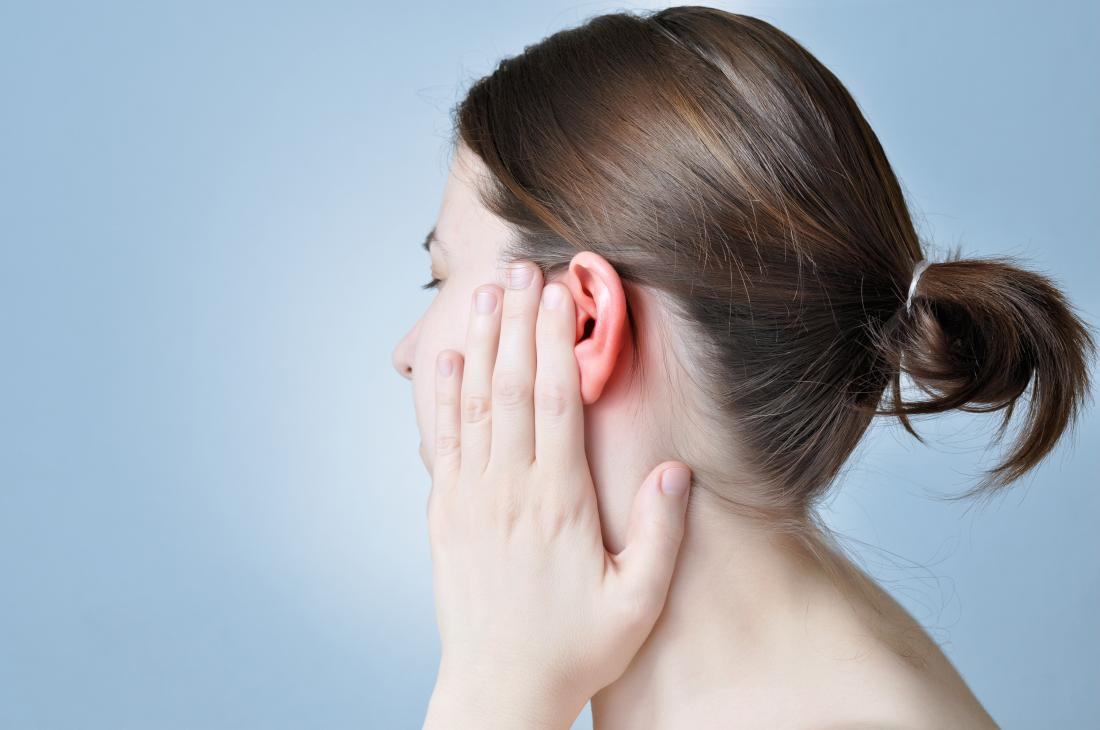 Donna che copre il suo orecchio dal dolore.