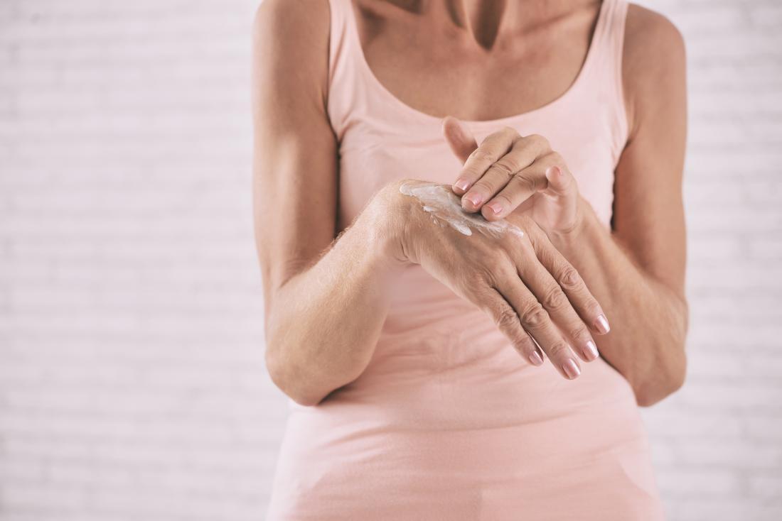 Kobieta stosuje śmietankę skóra na plecy jej ręka.