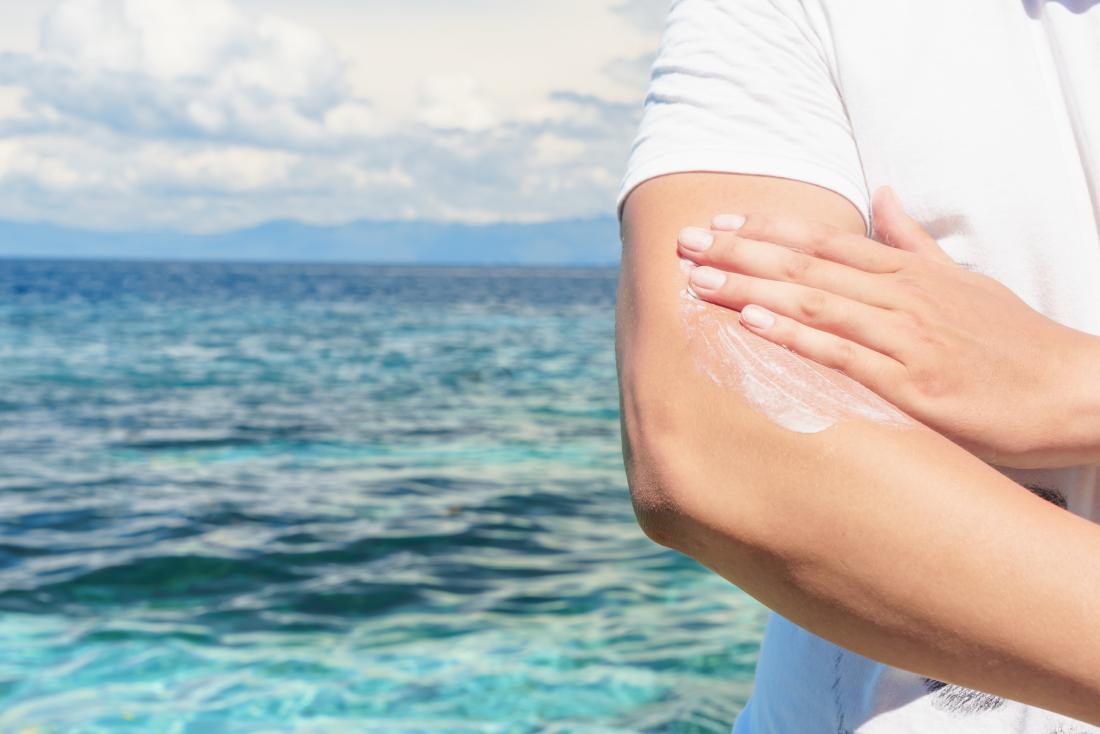 Mężczyzna kładzenia sunscreen na ręce przed oceanem.