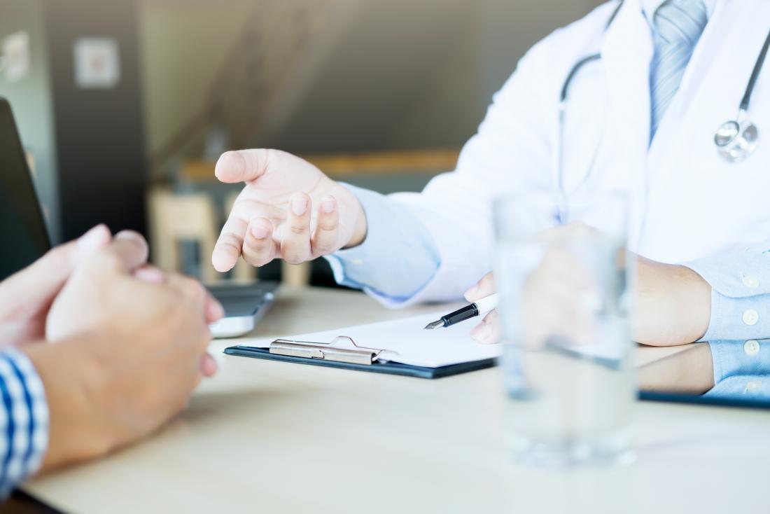 Doktor und Patient, die über Behandlung des Zustandes konsultieren.