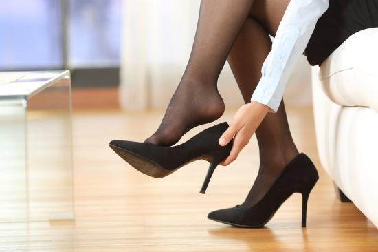 Uma mulher tirando os sapatos de salto alto