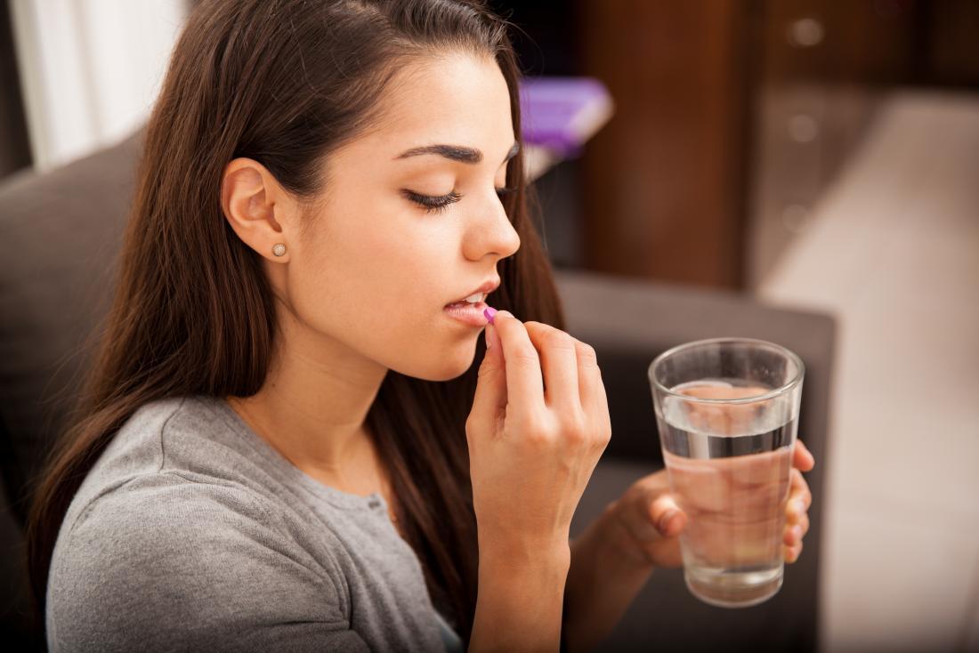 jeune femme prenant une pilule avec un verre d'eau