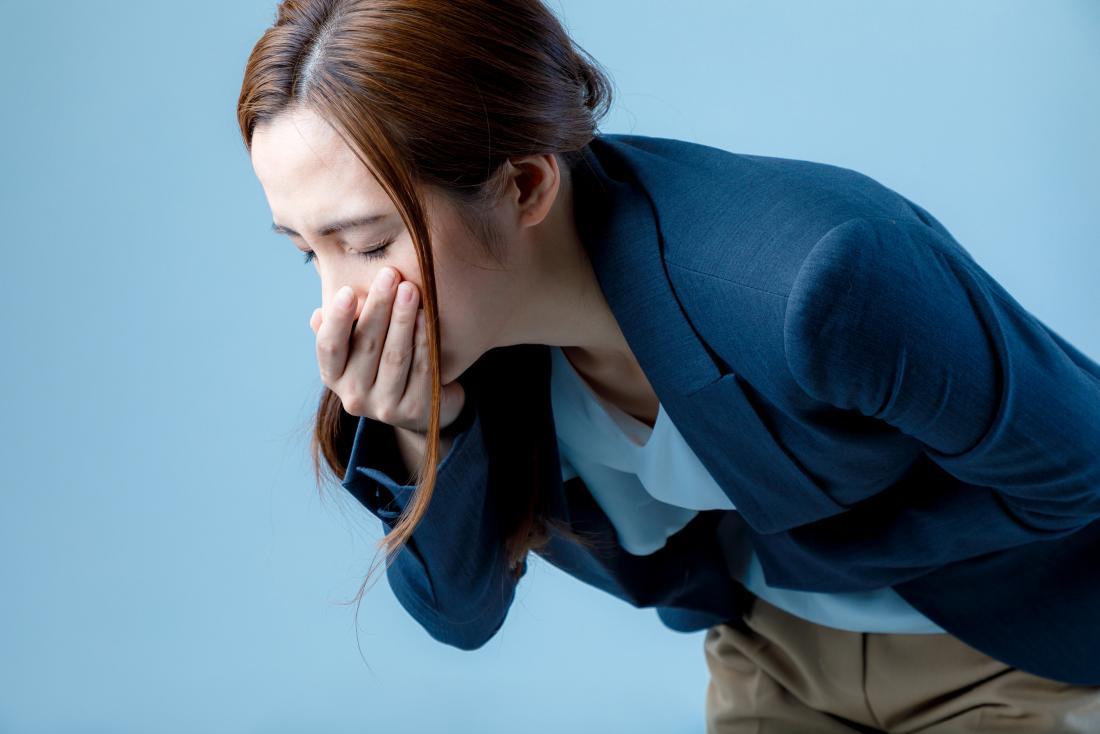 女性は二重に曲がって、彼女の口の上に手を持ち、乾いた盛り上がり、病気になる。