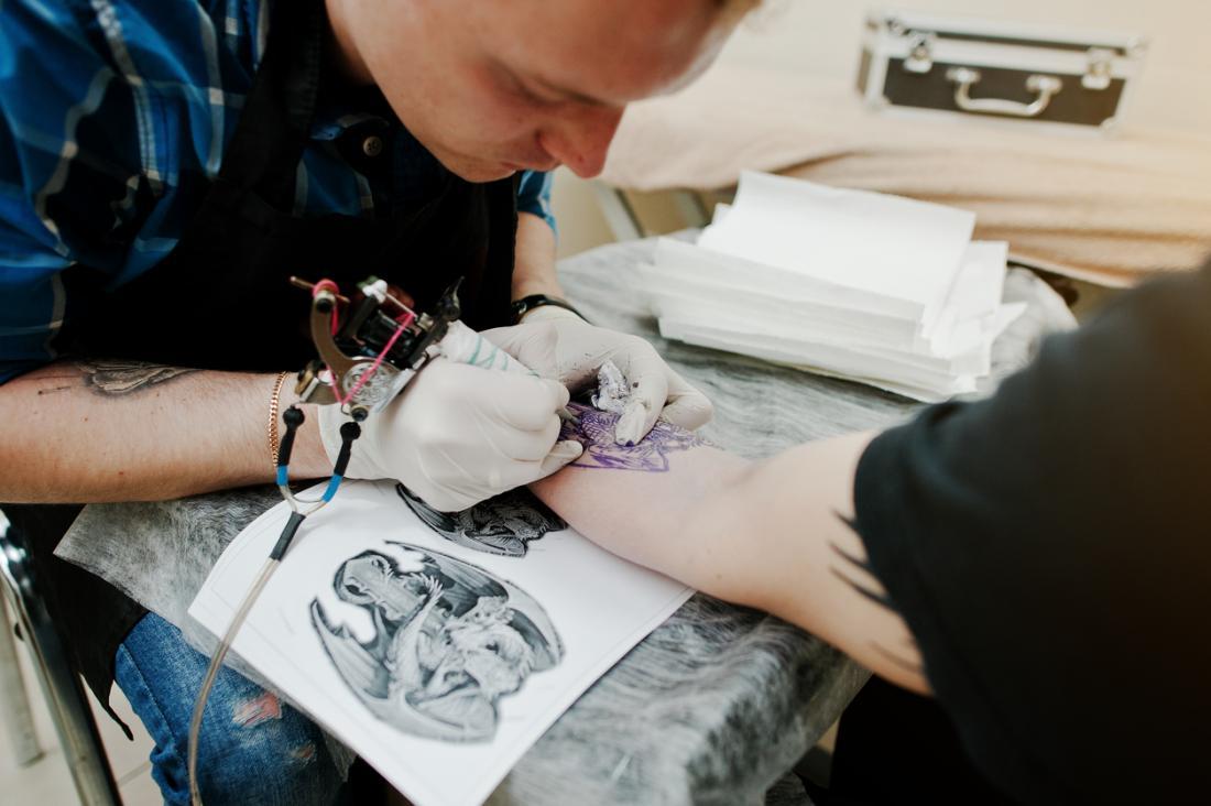 Tätowierungskünstler, der Tinte auf den Arm einer Person unter Verwendung der Nadeln anwendet