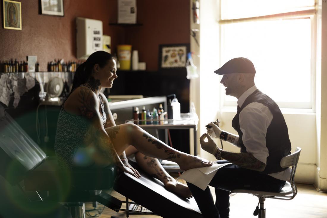 Tätowierungskünstler, der mit Kunden im Wohnzimmerstudio spricht.