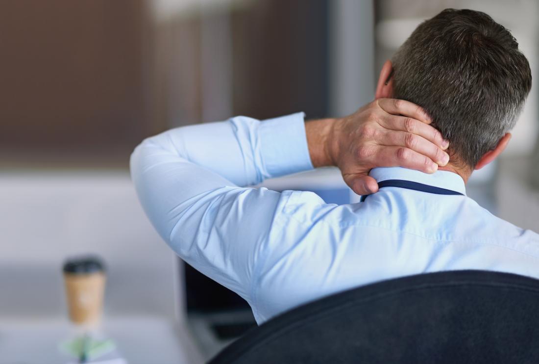 Người đàn ông với crick trong cổ giữ lại cổ trong khi ngồi ở bàn làm việc.