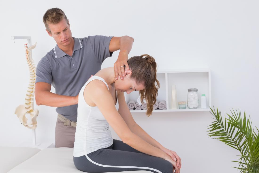 Người phụ nữ nhận vật lý trị liệu từ chiropractor đến cổ và trên lưng.