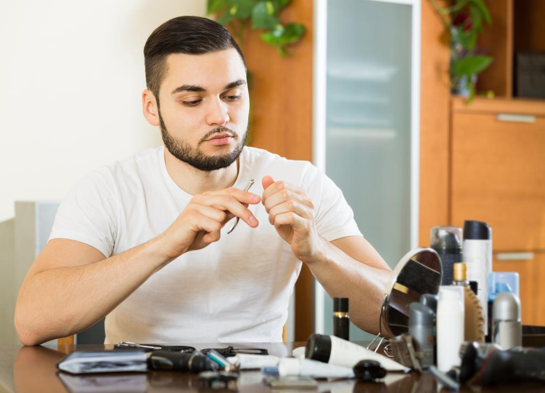 Người đàn ông kiểm tra hangnail bị nhiễm bệnh, với các sản phẩm làm sạch cát và làm móng tay trên bàn trước mặt anh ta.