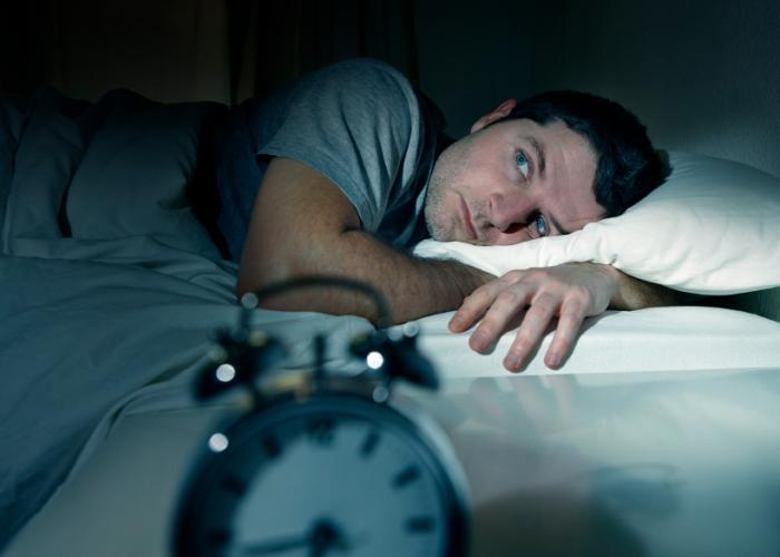 [uomo che ha problemi a dormire con la sveglia in primo piano]
