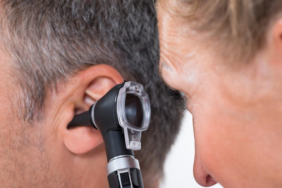 Doutor que examina uma orelha dos pacientes com um otoscope.