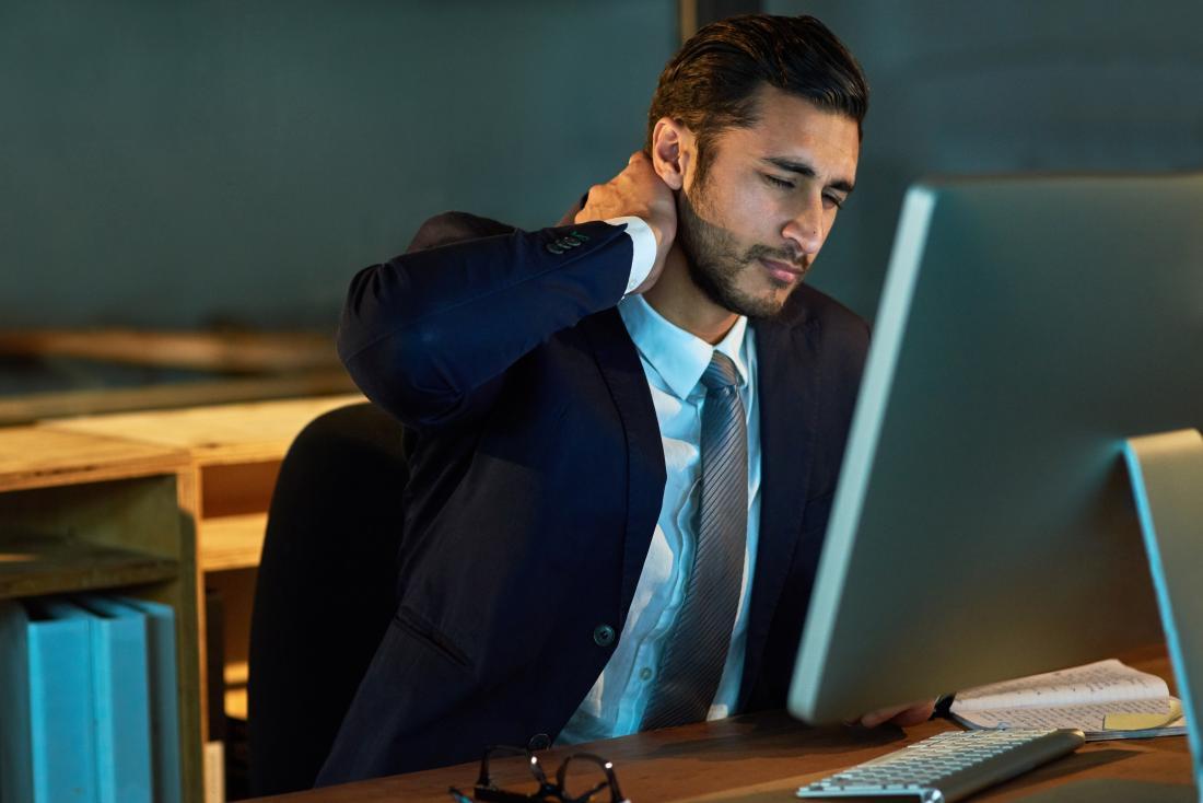 Người đàn ông bị đau cơ cổ ngồi trong ghế văn phòng.