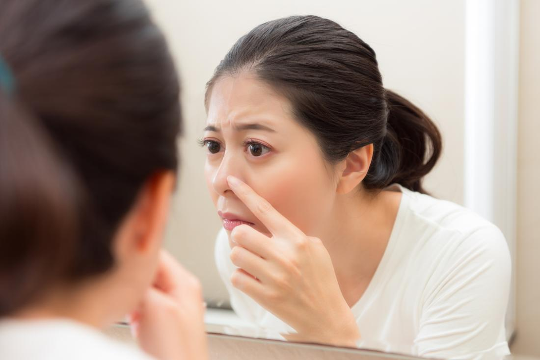 Kobieta sprawdza whitehead na nosie w łazienki lustrze.