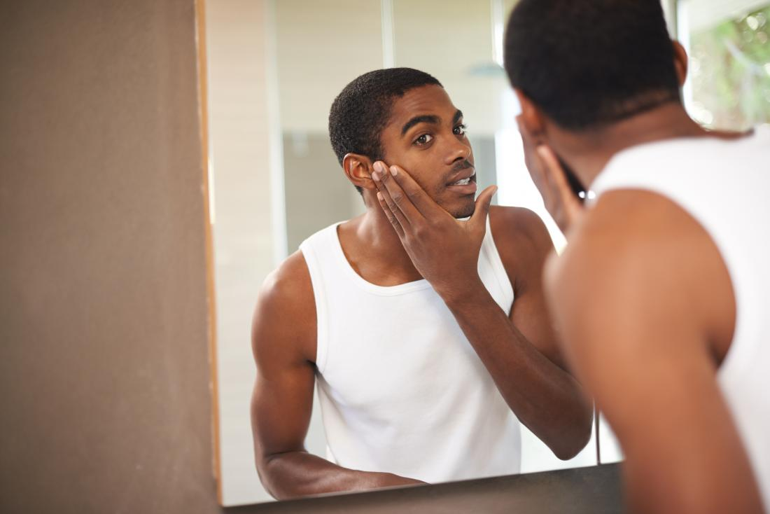 Mężczyzna patrzeje w lustrze sprawdzać jego twarz i stawiać produkt dalej.