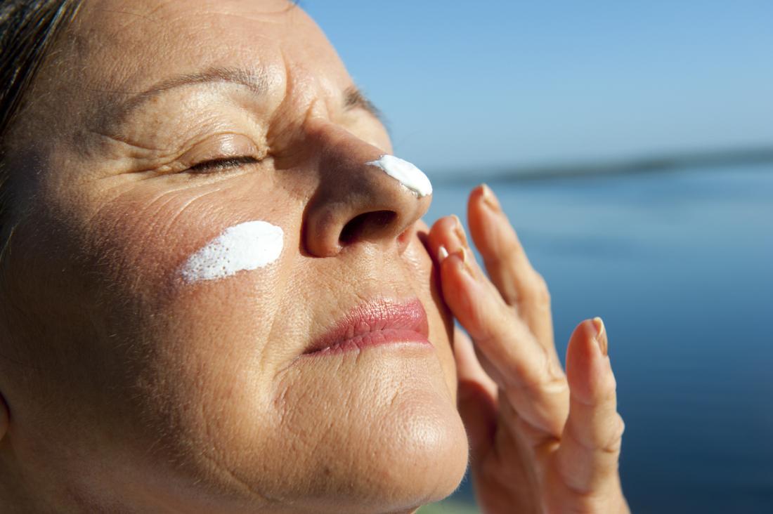 dame plus âgée applique la crème solaire