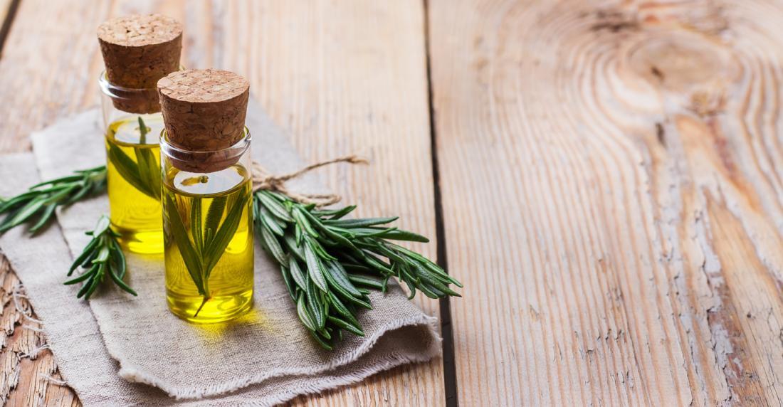 Brin de romarin et huile de romarin dans des bouteilles claires sur la table en bois.