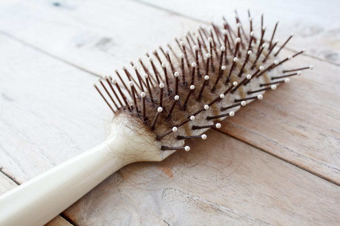 Brosse à cheveux avec beaucoup de mèches de cheveux sur la table en bois.