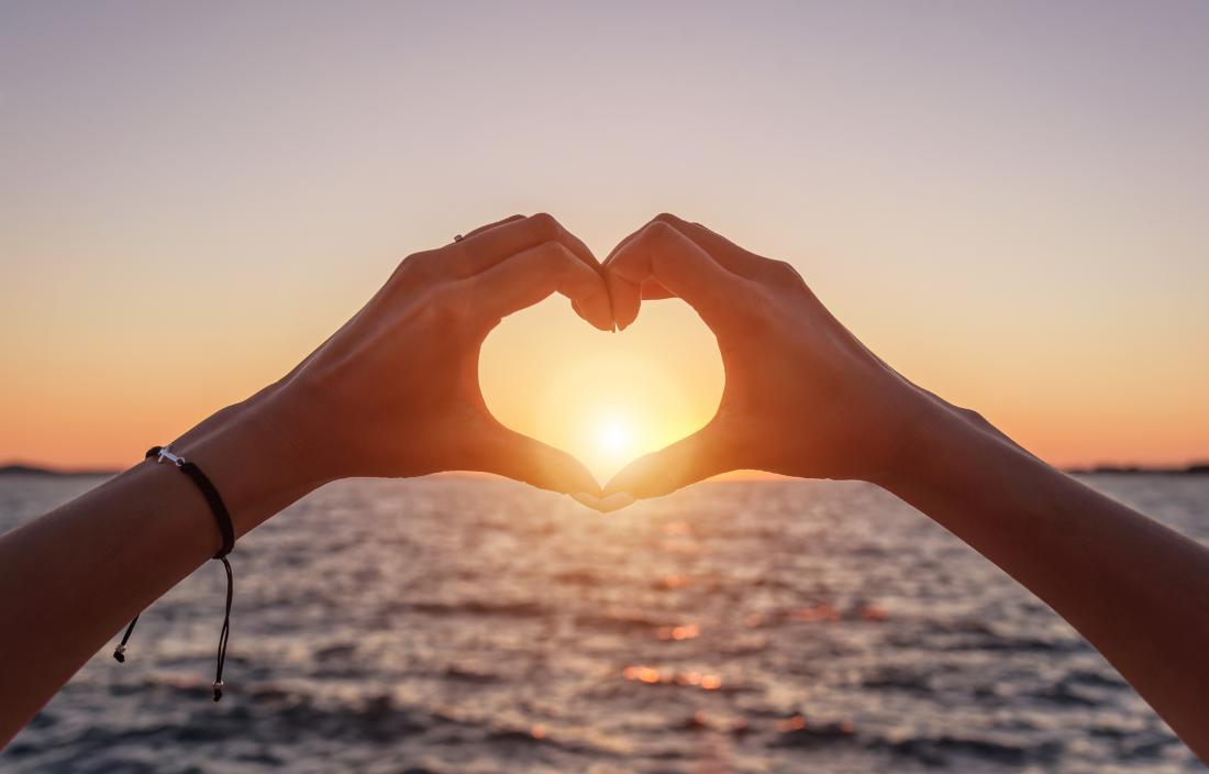 Coucher du soleil entre les mains du cœur et la mer