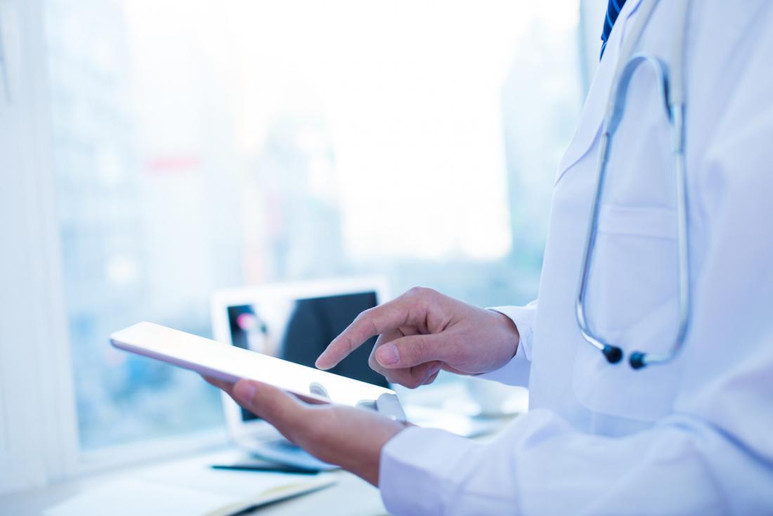 médecin vérifiant les notes sur une tablette