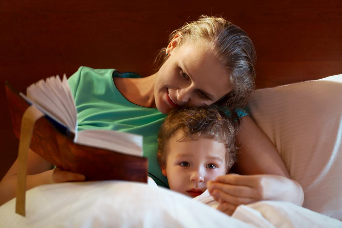 Mutter liest zu ihrem Kind vor dem Schlafengehen