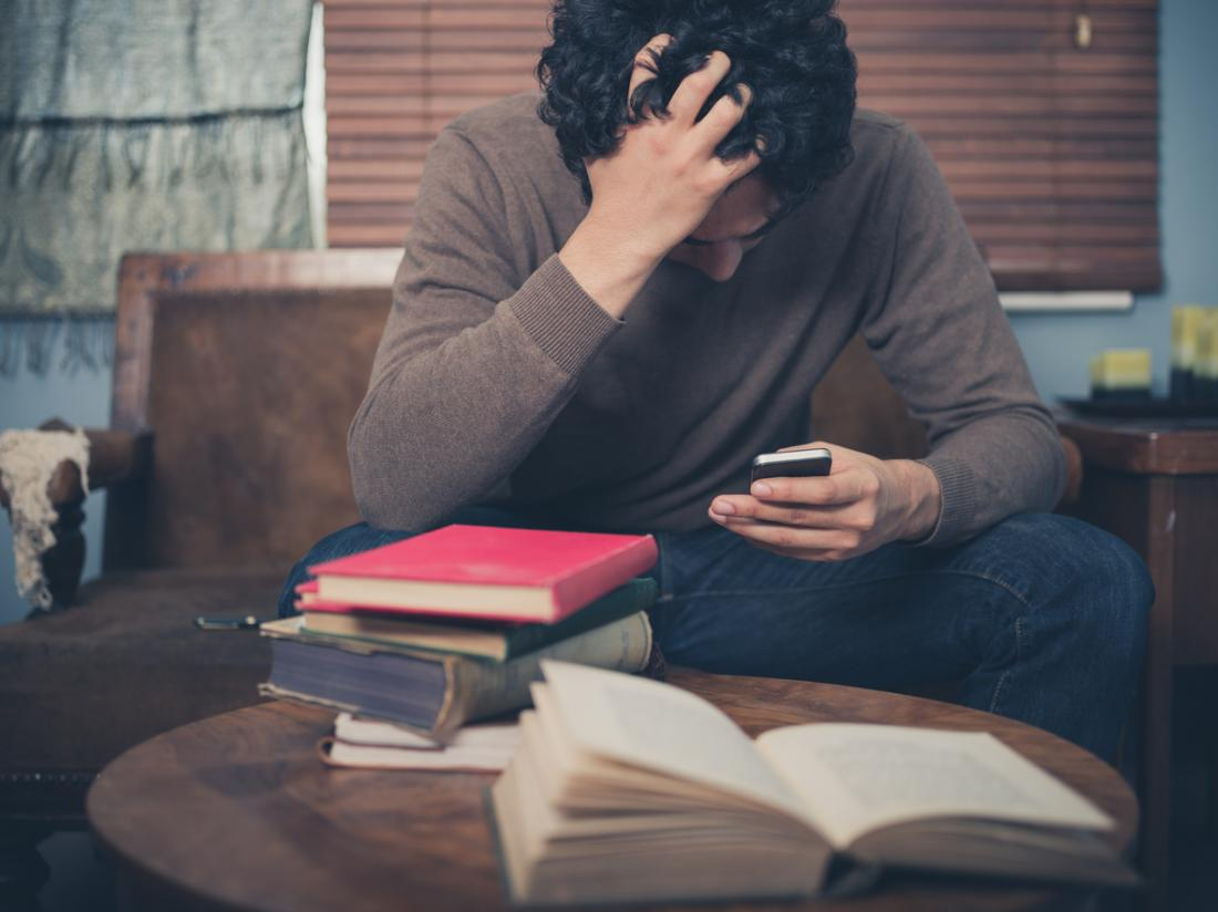 deprimierter Mann, der sein Telefon betrachtet