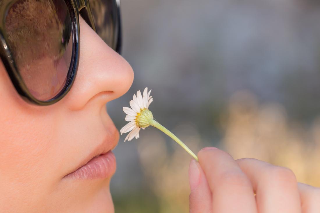 女性は花を嗅ぐ。
