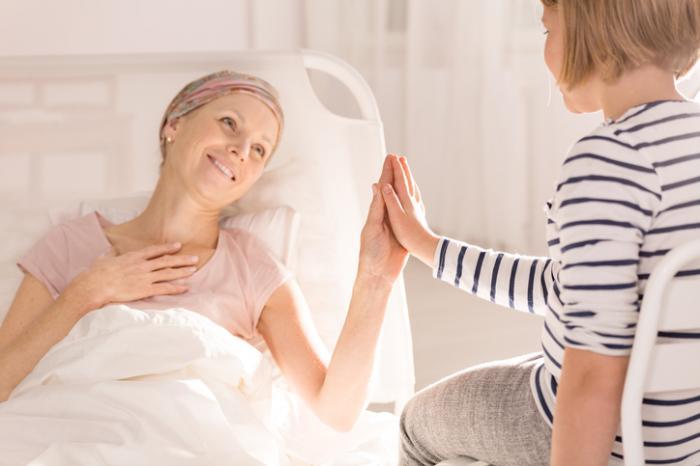 [Femme atteinte du cancer du sein assise avec son enfant]
