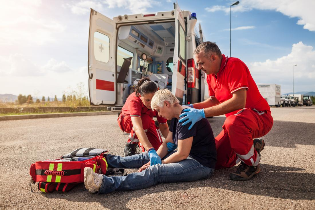 Personne aidée par les ambulanciers et les ambulanciers après une blessure sur une route ou une rue.