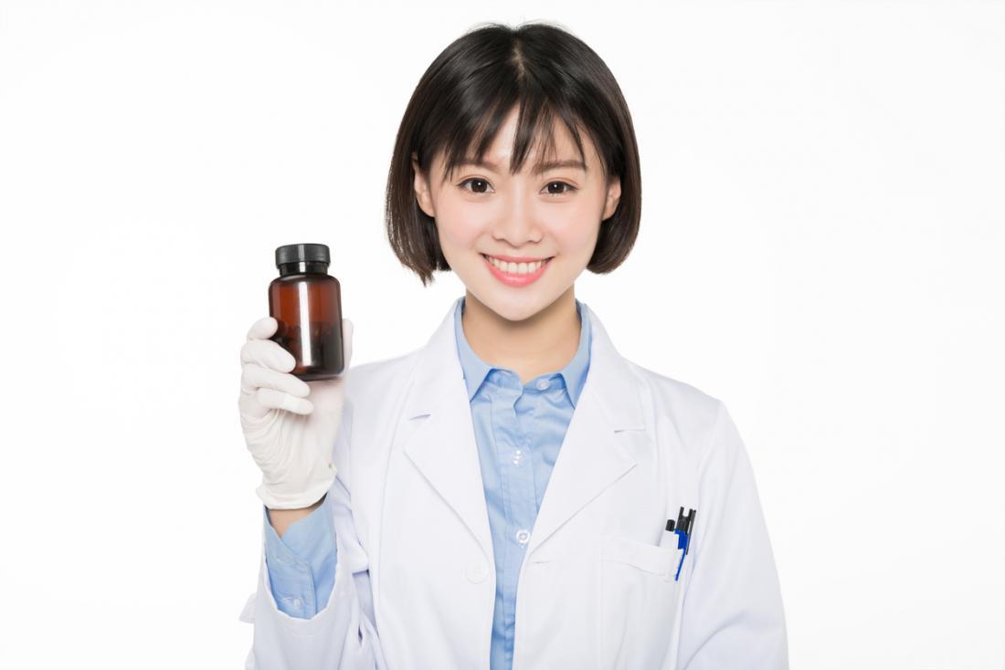 医者は丸薬のボトルを保持します。