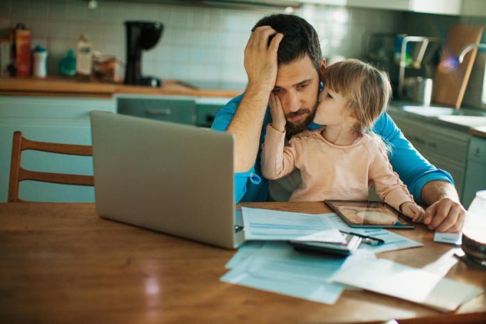 човек използва лаптопа си, който изглежда тъжно, докато дъщеря му седи в скута му и го целува по бузата