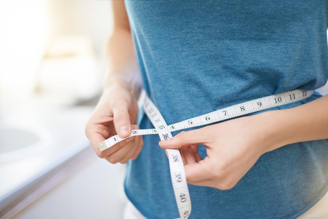 Personne essayant de perdre du poids en mesurant sa taille.
