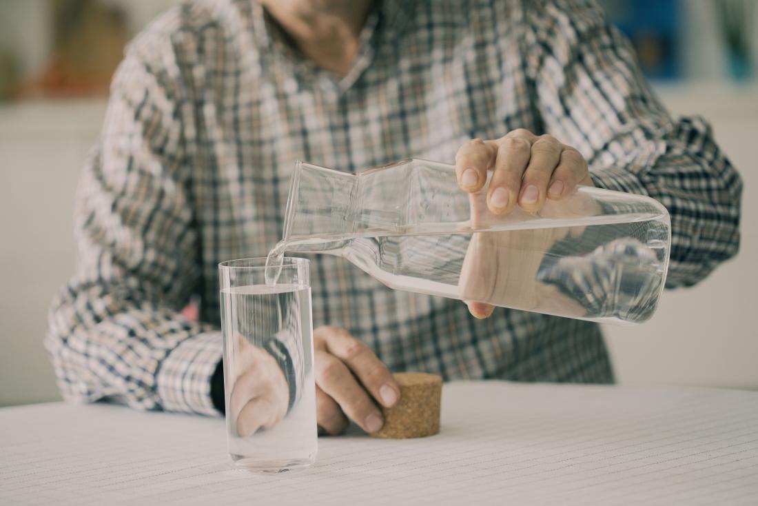 uomo anziano che versa e acqua potabile a un tavolo da cucina