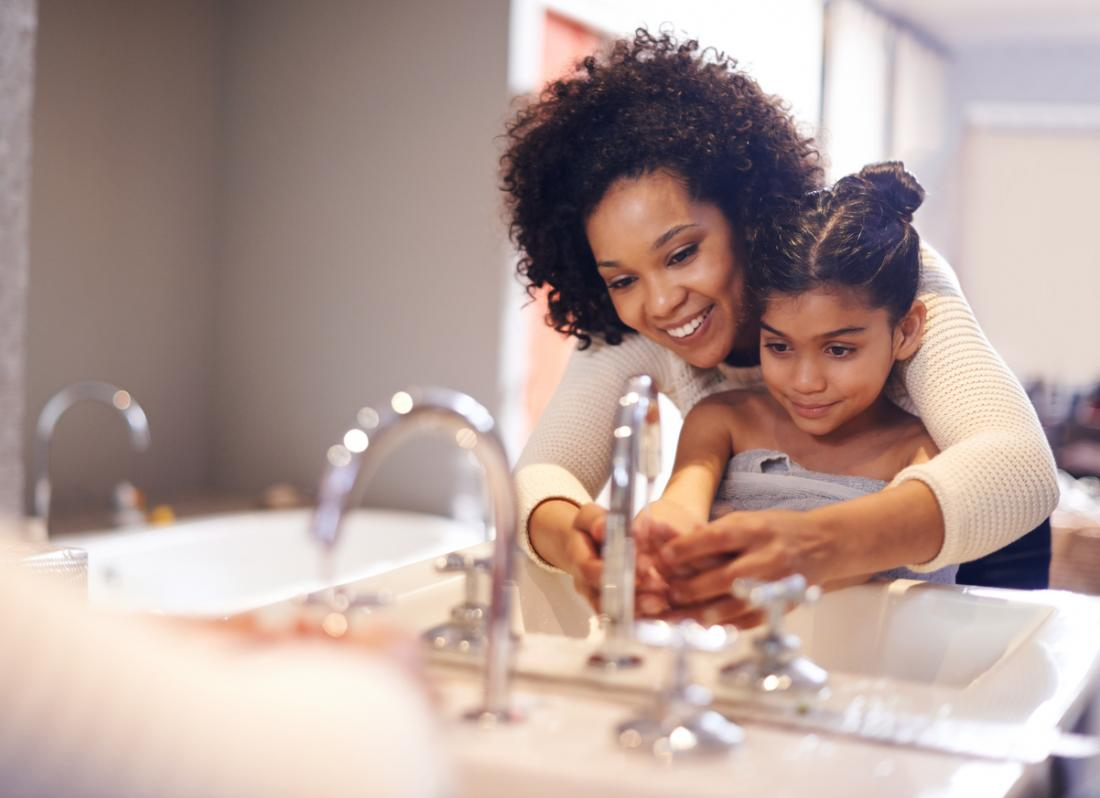 madre che aiuta sua figlia a lavarsi le mani