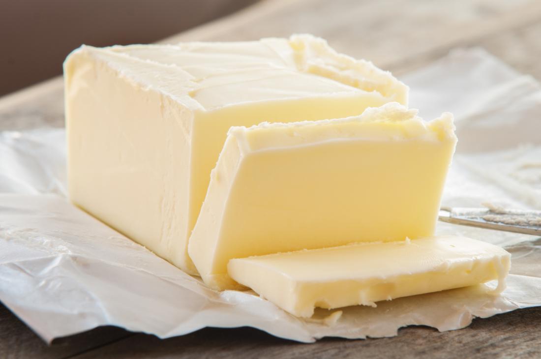 Bloc de beurre sur l'emballage partiellement tranché.