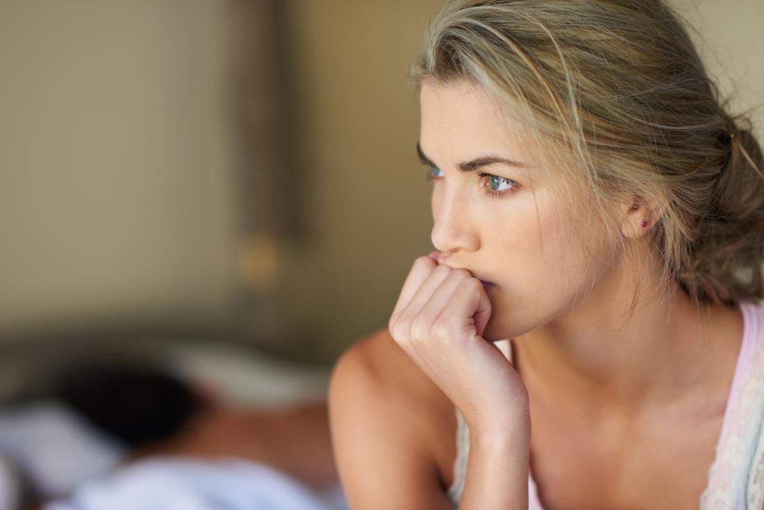la donna è preoccupata nella sua camera da letto probabilmente per sanguinamento dopo il sesso
