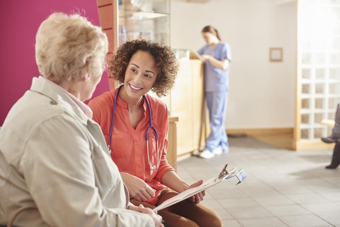 Възрастна жена разговаря с лекар в чакалнята.