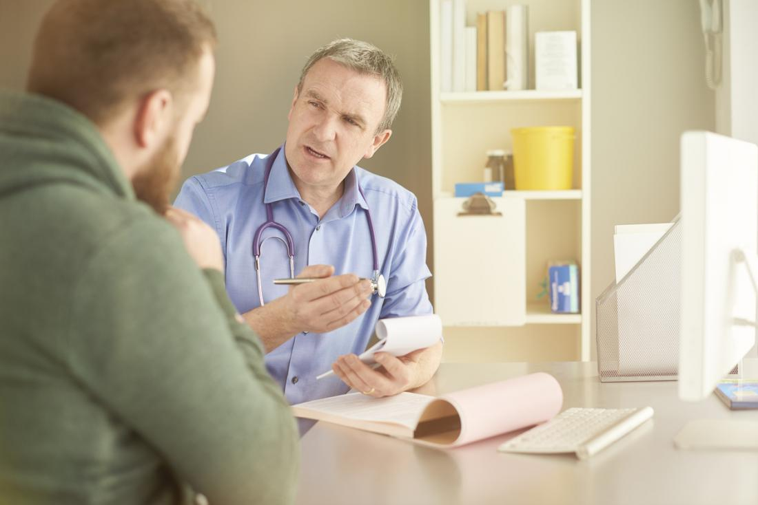 Bác sĩ nam chính với notepad giải thích điều gì đó cho bệnh nhân nam trẻ