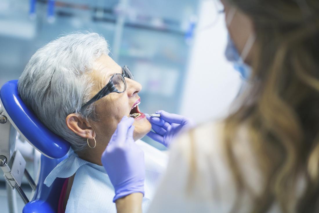 Ältere Frau, die eine Überprüfung der Mundhygiene am Zahnarzt hat.