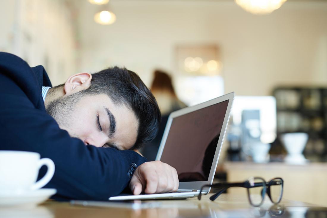 Homme endormi au bureau devant un ordinateur portable et une tasse de café.