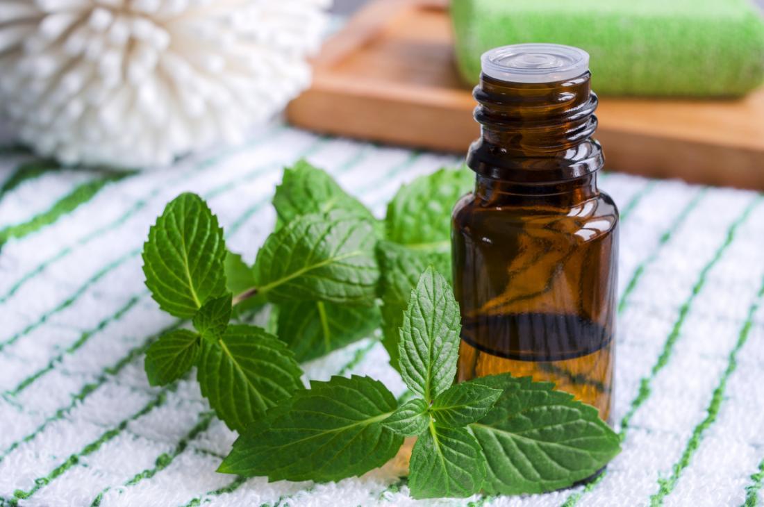 feuilles de menthe poivrée à côté de la petite bouteille d'huile essentielle.