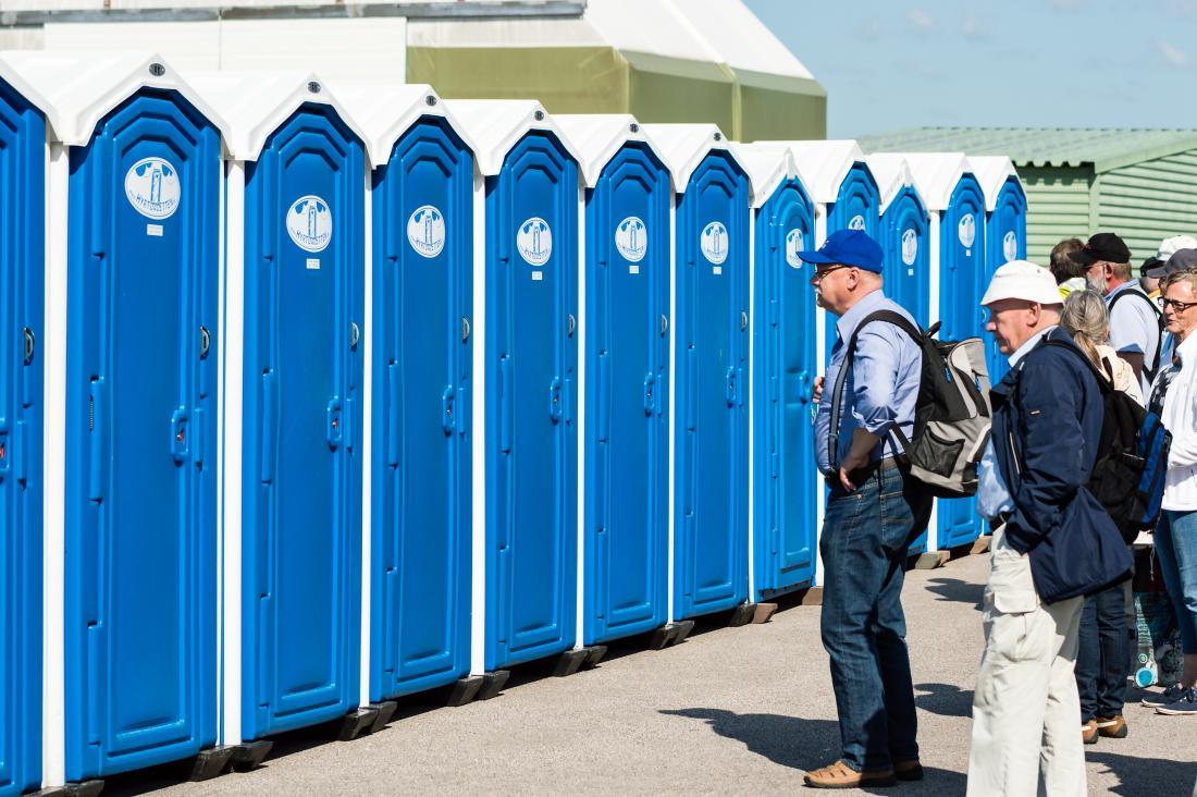 Tuvaletler için bir sıra halinde işemek tutan insanlar