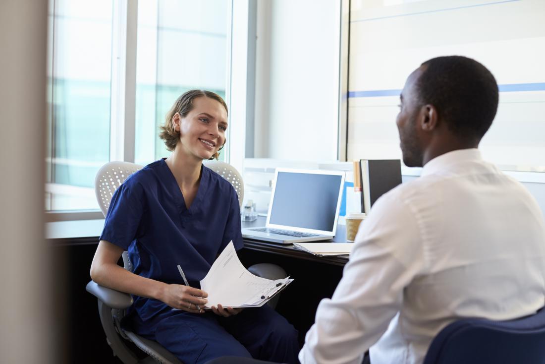 Mann, der mit Doktor in ihrem Büro lächelt beide spricht.