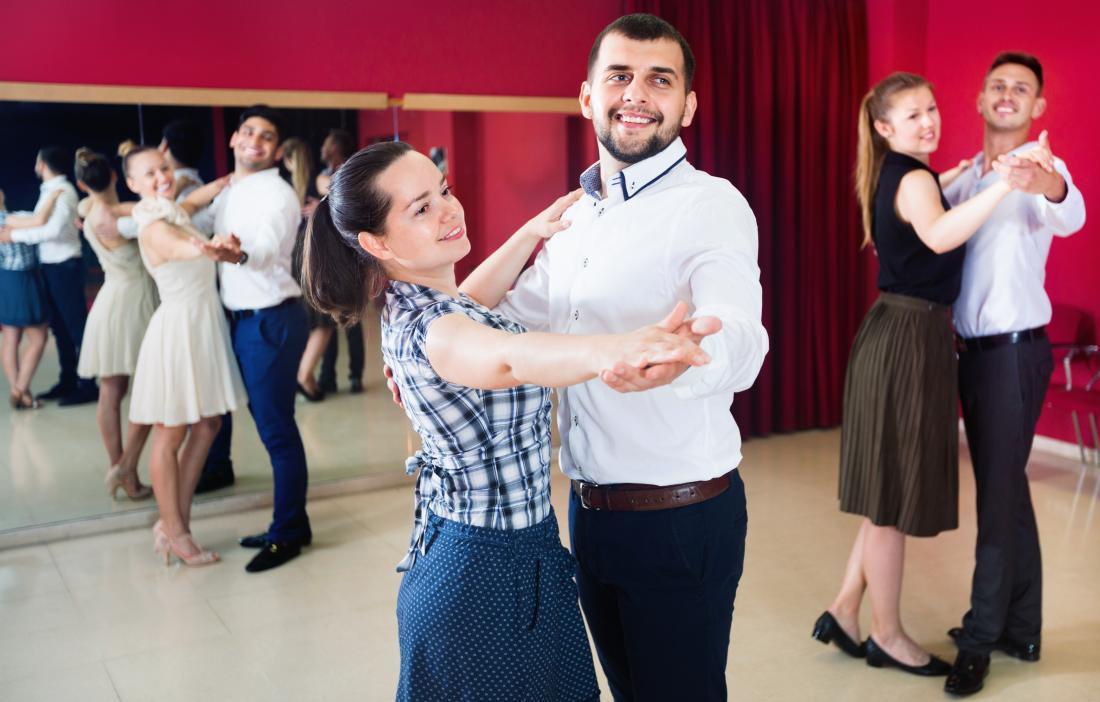 Млади двойки, които учат танци в балната зала.