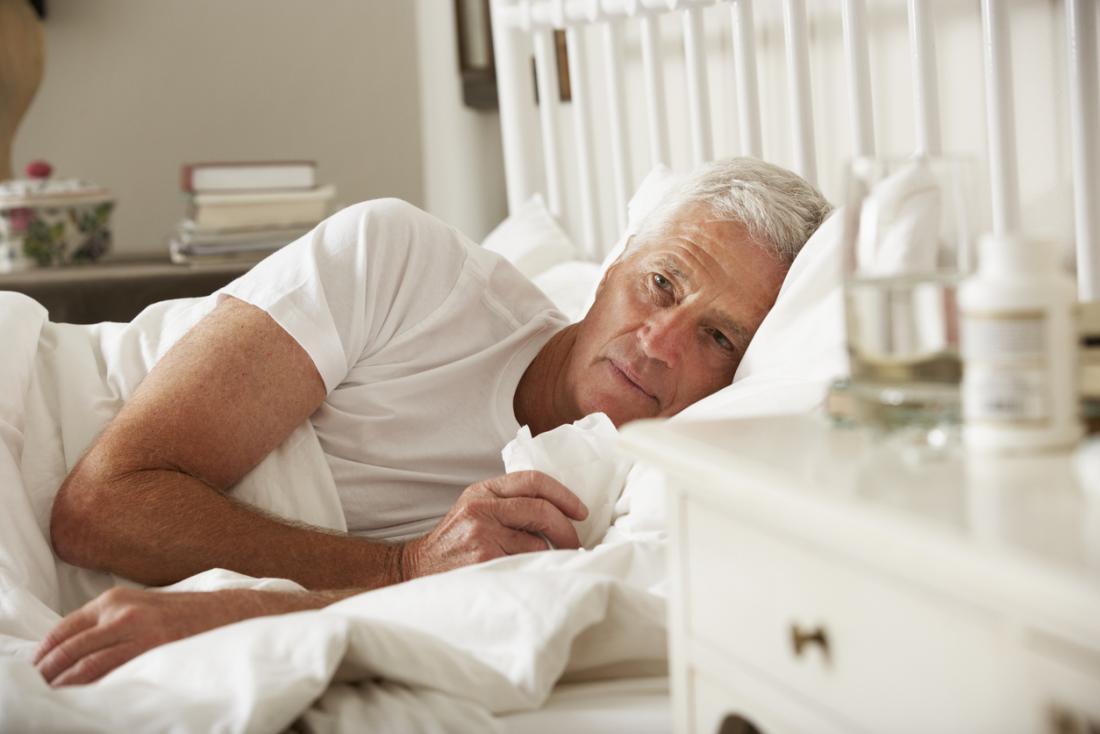 starszy mężczyzna w łóżku z grypą